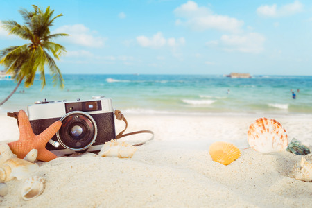 The concept of leisure travel in the summer on a tropical beach seaside. retro camera on the sandbar with starfish, shells, coral on sandbar and blur sea background.  vintage color tone styles. Фото со стока