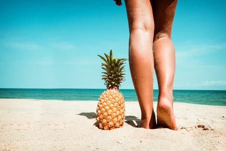 휴식과 여름에 레저 - 파인애플 여름에 열 대 해변에서 서있는 젊은 여자의 무두 질된 다리. 빈티지 색조 효과 스톡 콘텐츠