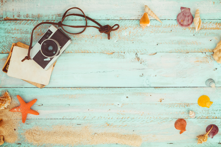 Summer background - The concept of leisure travel in the summer on a tropical beach seaside. retro camera with starfish, shells, coral on wood table background.  vintage color tone styles.