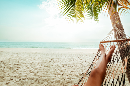 women legs: Leisure in summer - Beautiful Tanned legs of sexy women. relax on hammock at sandy tropical beach. vintage color styles Stock Photo