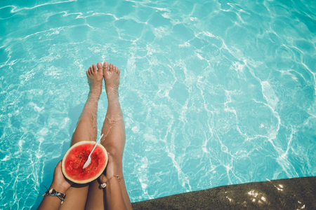 summer fruit: Relaxation and Leisure - Lifestyle in summer of Tanned girl holding watermelon (Tropical fruit) in the blue pool. Summer holiday idyllic.