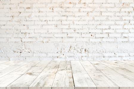 Tabela de madeira branca clara vazia para a colocação do produto ou a montagem, estilo da perspectiva. fundo branco da parede de tijolo do vintage.