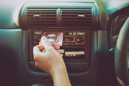Woman hand holding tape cassette in car for driving listen music - vintage color tone effect.
