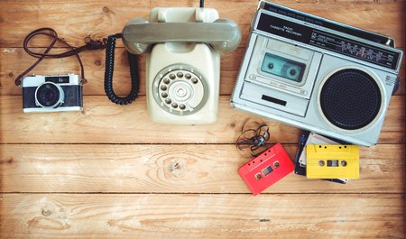 Top view hero header - retro technology of radio cassette recorder with retro tape cassette, vintage telephone and film camera on wood table. Vintage color effect styles.