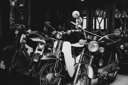 Old and Classic motorcycle parked in garage. Vintage black and white color tone effect.