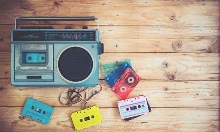 頂視圖英雄頭 - 復古技術的收音機錄音機音樂與復古磁帶盒在木桌上。復古色效果風格。