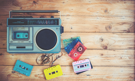 Top view hero header - retro technology of radio cassette recorder music with retro tape cassette on wood table. Vintage color effect styles.