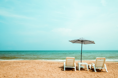Couple beach chair on tropical beach. vintage color tone effect Stock Photo