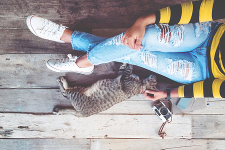 Hipster lifestyle - Girl in jeans with retro camera and cat sit on the wooden floor. vintage film color effect and retro color style