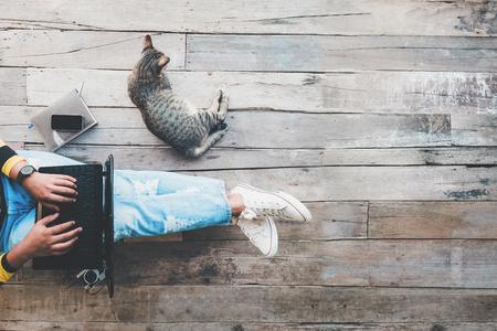 Hipster 라이프 스타일과 크리 에이 티브 작업 공간 - 나무 바닥에 그녀의 고양이에 의해 지원 랩톱 컴퓨터에서 작동하는 청바지 소녀. 빈티지 필름 색상  스톡 콘텐츠