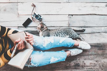 Hipster 라이프 스타일 - 복고풍 카메라, 스마트 전화 및 고양이와 일기를 작성하는 청바지에 소녀 나무 바닥에 앉아. 빈티지 필름 색상 효과와 레트로 컬