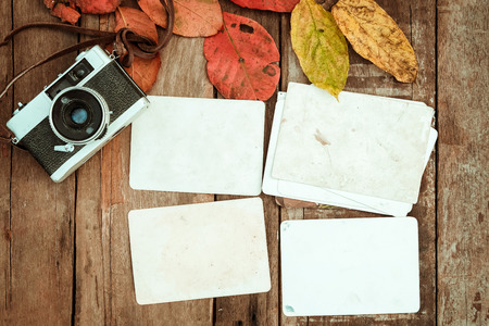 Retro camera and empty old instant paper photo album on wood table with maple leaves in autumn border design - concept of remembrance and nostalgia in fall season. vintage rustic style. Stock fotó
