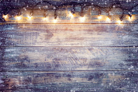 Christmas lights bulb with snow on wood table. Merry christmas (xmas) background. topview, border design - rustic and vintage styles