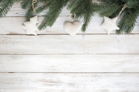 Christmas background - fir leaves and decoration rustic elements on white wood table. Creative Flat layout and top view composition with border and copy space design. Banco de Imagens