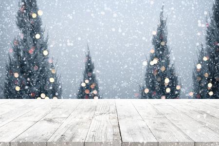ウッドデッキ テーブル クリスマス ツリー、雪、ぼやけた光ボケとクリスマスと新年の背景。製品のモンタージュの空が表示されます。素朴なヴィ 写真素材
