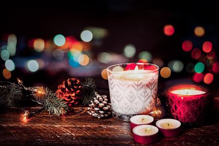 크리스마스 배경 - 크리스마스 촛불와 밤 파티에서 크리스마스 조명 배경으로 나무 테이블에 소박한 장식. 빈티지 색상 스타일입니다.