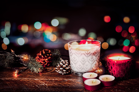 Christmas background - Christmas candle and rustic decoration on wood table with christmas lights background in night party. vintage color style.