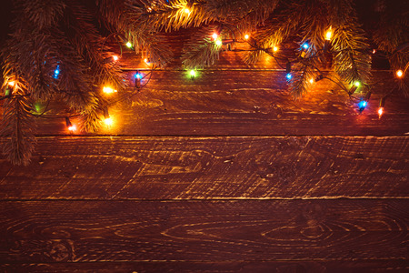 Christmas tree and colorful lights bulb. Merry christmas (xmas) background. Old wood texture - vintage styles Reklamní fotografie