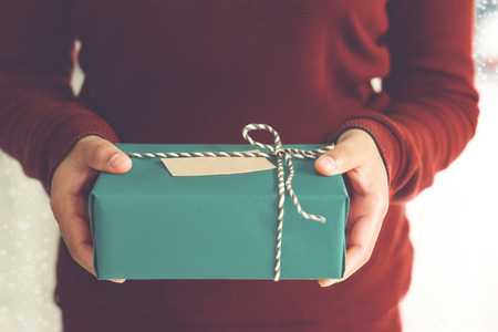 Woman hands holding Christmas handmade gift box or new year present with snow background. vintage color tone