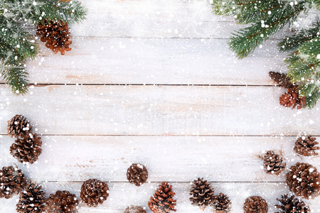 Christmas background - fir tree and pine cones decorating rustic elements on white wood table with snowflake. Creative Flat layout and top view composition with border and copy space design.