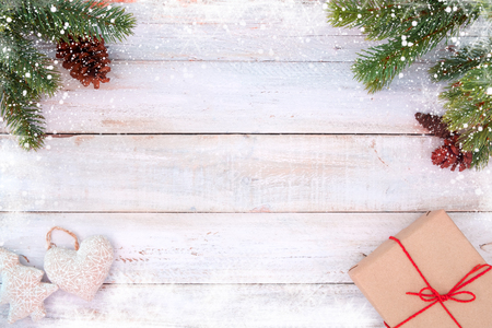 Christmas background - fir leaves and pine cones decorating rustic elements on white wood table with snowflake. Creative Flat layout and top view composition with border and copy space design.