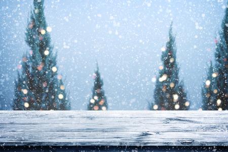 크리스마스와 새 해 배경 크리스마스 나무, 눈과 흐릿한 조명 bokeh 통해 나무 갑판 테이블. 제품 몽타주에 대 한 빈 표시입니다. 소박한 빈티지 크리스