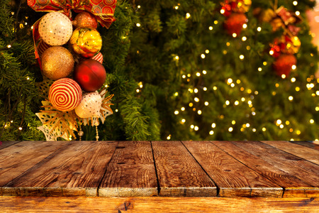 Christmas tree background with decoration and blurred light bokeh with empty dark wooden deck table for product montage. Rustic vintage Xmas background. 免版税图像