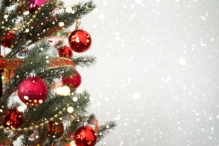 Close-up of Christmas tree with ornament, decoration and light bokeh with snowfall on winter background