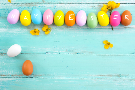 Colorful Easter eggs with flower on rustic wooden planks background in blue paint. Holiday in spring season. vintage pastel color tone. top view composition. Stok Fotoğraf