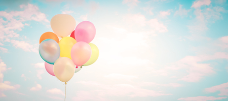 Vintage multicolor balloons with done with a retro filter effect on blue sky. Ideas for web banner background. Love in summer and valentine, wedding honeymoon concept. Stock Photo