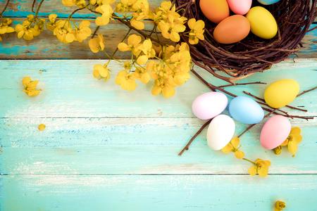 Ovos da páscoa coloridos no ninho com a flor no fundo de madeira rústico das pranchas na pintura azul. Férias na temporada de primavera. estilo vintage tom de cor. composição da vista superior.