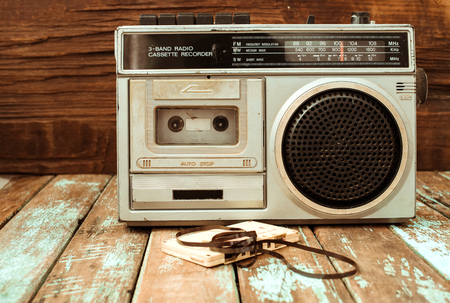Retro technology of radio cassette recorder music with retro tape cassette on wood table. Vintage color effect styles.
