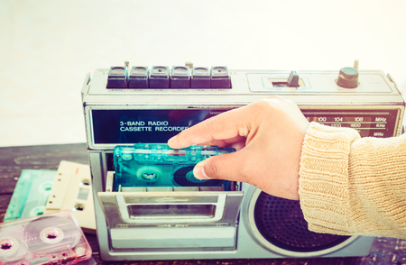 Retro lifestyle - Woman hand holding tape cassette with cassette player and recorder for listen music - vintage color tone effect. 版權商用圖片