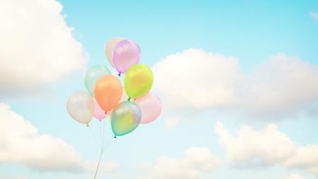 Palloncini multicolori vintage con fatto con un effetto filtro retrò sul cielo blu. Idee per lo sfondo dell'amore in estate e San Valentino, concetto di luna di miele di nozze. Archivio Fotografico