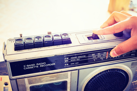 Retro lifestyle - Womans hand switched and adjusting button cassette player and recorder for listen music - vintage color tone effect. Banco de Imagens