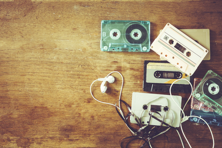 Retro technology of cassette recorder music with retro tape cassette on wood table. Vintage color effect styles.