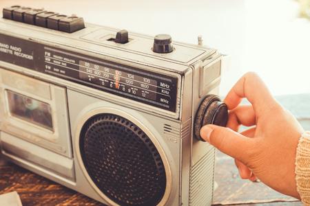 Retro- Lebensstil - die Hand der Frau, die Knopfkassettenrecorder und -recorder für justiert, hören Musik - Weinlesefarbtoneffekt.