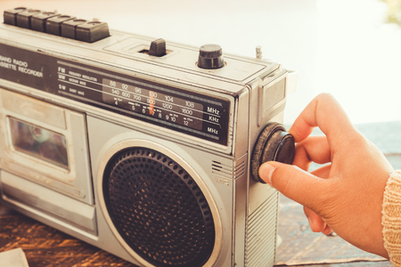 Retro lifestyle - Womans hand switched and adjusting button cassette player and recorder for listen music - vintage color tone effect. Фото со стока