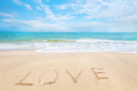 Inscription Love written on the sandy beach with ocean wave - honeymoon on beach concept.