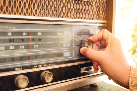 レトロなライフスタイル - 女性の手は、音楽やニュースを聴くためにボタンヴィンテージラジオ受信機を調整 - ヴィンテージカラートーン効果。