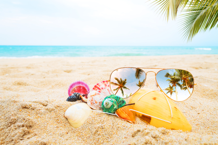 sunglasses and seashell on the sandy tropical beach with clear blue sky. Leisure in summer and Summer vacation concept. vintage color tone.