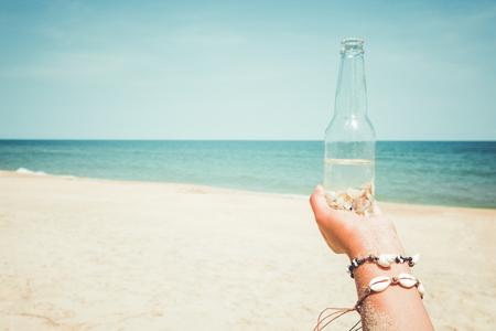 夏のリラクゼーションとレジャー - 夏に熱帯のビーチで貝殻とボトルを持つ若い日焼けした女性の手。ヴィンテージ色調効果