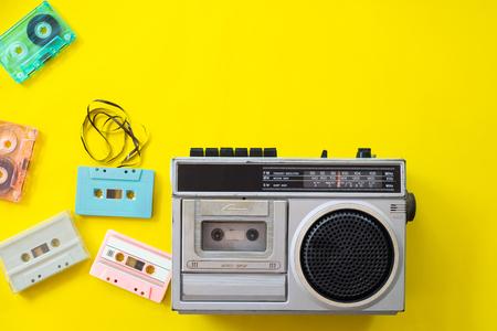 Radio vintage y reproductor de casetes sobre fondo amarillo, endecha plana, vista superior. tecnología retro