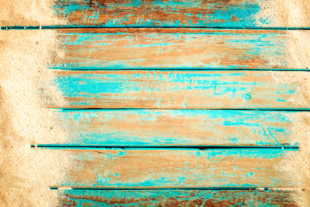 Beach background - top view of beach sand on old wood plank in blue sea paint background. summer vacation concept. vintage color tone. Stock Photo