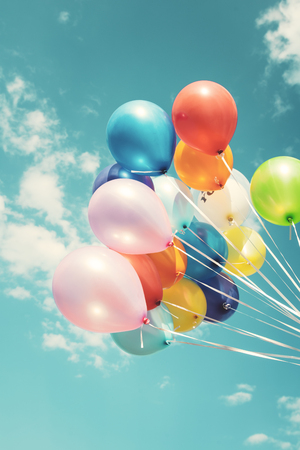 Colorful festive balloons over blue sky with a retro vintage filter effect.