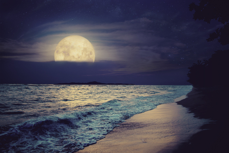Beautiful fantasy tropical sea beach. Full moon (super moon) with cloud over seascape in night skies. Serenity nature background at nighttime. vintage and retro color filter style. Stock Photo