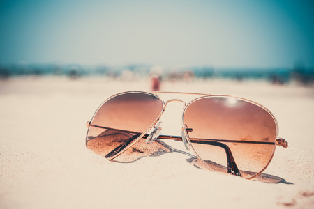 Vintage photo of nostalgia in summer - sunglasses on sand beach. retro film filter effect