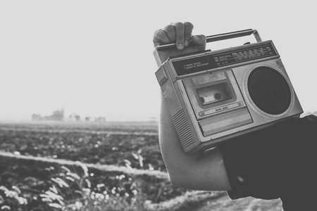 Photo of memorie and nostalgia. people with vintage radio or cassette reccorder in countryside. black and white color tone.