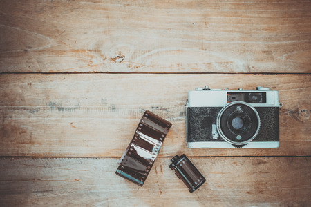 Photo of nostalgia - vintage film camera on old wooden background 写真素材
