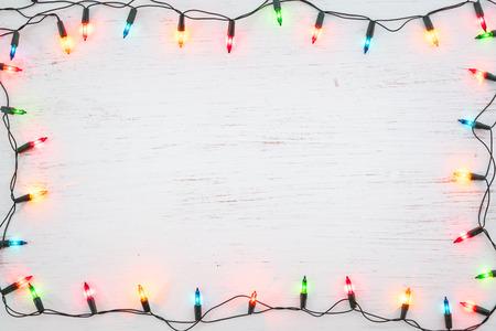 Kerstverlichting lamp frame decoratie op wit hout. Vrolijke Kerstmis en Nieuwjaar vakantie achtergrond. bovenaanzicht